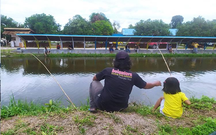 Pengunjung kolam pemancingan, seorang bapak dan putrinya memancing ikan bersama di Kolam Pemancingan Lewu Panatau, Minggu, 23 Mei 2021.