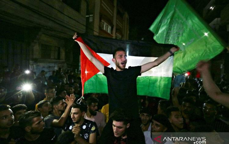 Warga Palestina turun ke jalan merayakan gencatan senjata di Jalur Gaza Selatan, Kamis (20/5/2021)