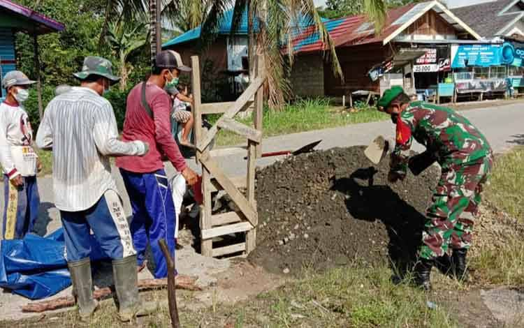 Babinsa Koramil 1013-03 Teweh Tengah membantu warga mengaduk semen untuk perbaikan jalan di wilayah Taman Remaja Muara Teweh, Selasa, 8 Juni 2021.