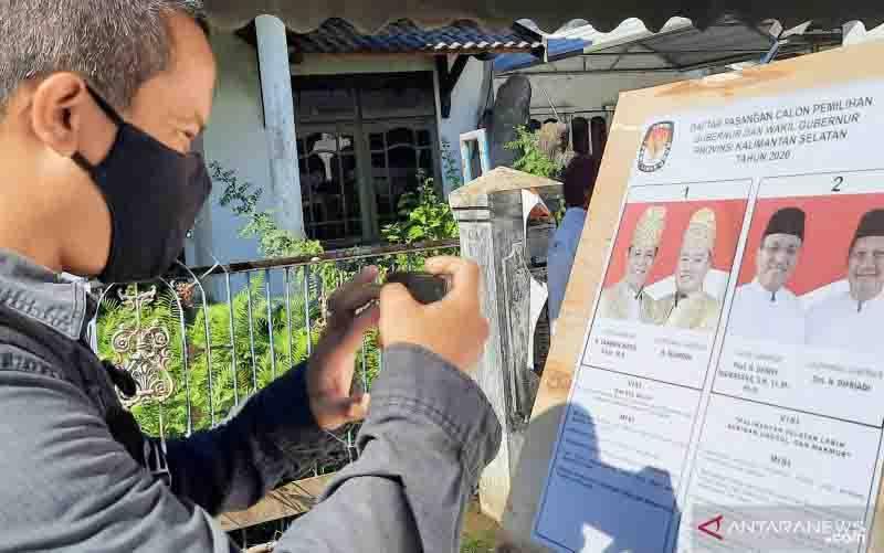 Seorang warga mengambil foto contoh kertas surat suara di TPS 06 Kelurahan Pemurus Dalam, Kecamatan Banjarmasin Selatan, Kota Banjarmasin. (foto : ANTARA/Firman)