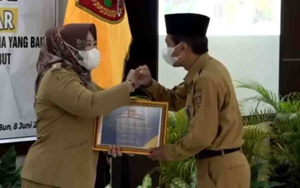 Bupati Kobar, Nurhidayah menyerahkan piagam penghargaan kepadaKepala BPKAD, Rochim Hidayat,atas dukungan dalam raihan Opini WTP.