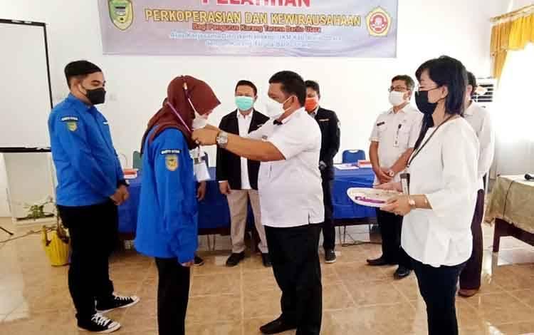 Kepala Dinas Nakertranskop UKM Barito Utara M Mastur mengalungkan tanda peserta kepada perwakilan peserta Karang Taruna yang mengikuti pelatihan perkoperasian dan kewirausahaan, di aula Disnakertranskop UKM setempat, Kamis 10 Juni 2021