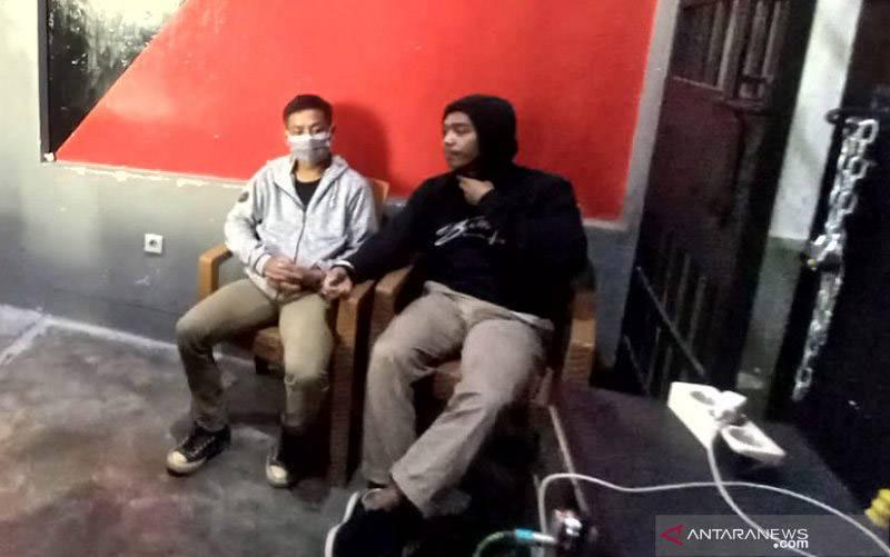 Pelaku terduga pemerasan berinisial MA (kanan) yang menjalankan modusnya dengan mengancam akan menyebar video porno korban ketika diamankan di Mapolresta Mataram, NTB, Rabu (9/6/2021). (foto : ANTARA/Dhimas B.P.)