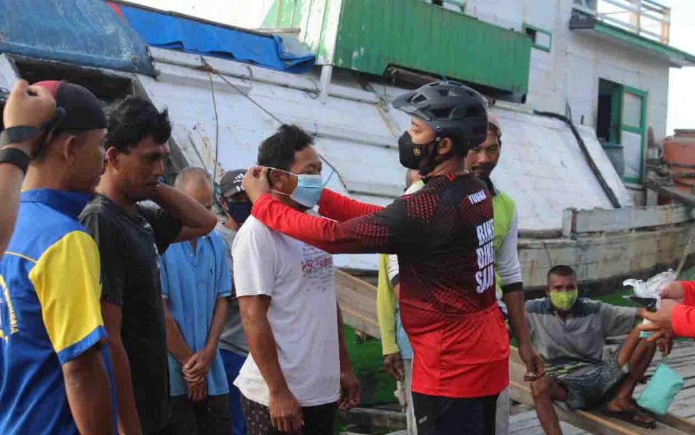 Kapolres Seruyan memasangkan masker kepada salah satu warga di Dermaga Bongkar Muat Kuala Pembuang, Jumat 11 Juni 2021