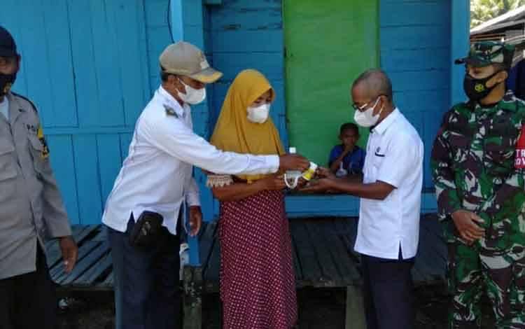 Pemdes Tamban Baru Timur saat menyerahkan sejumlan peralatan kesehatan untuk cegah covid-19 kepada warga.