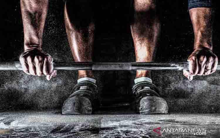 Ilustrasi - seorang atlet bersiap mengangkat barbel di gym