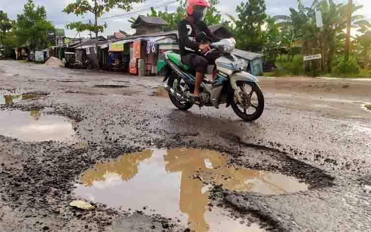 Seorang pengendara sepeda motor berusaha menghindari lubang-lubang berbahaya di Jalan Kapten Mulyono, Sampit
