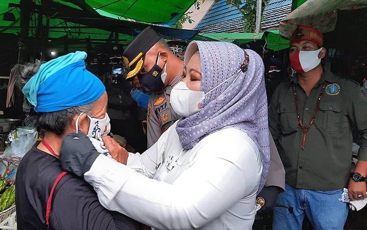 Bupati Kobar saat membagikan masker pada pedagang pasar.