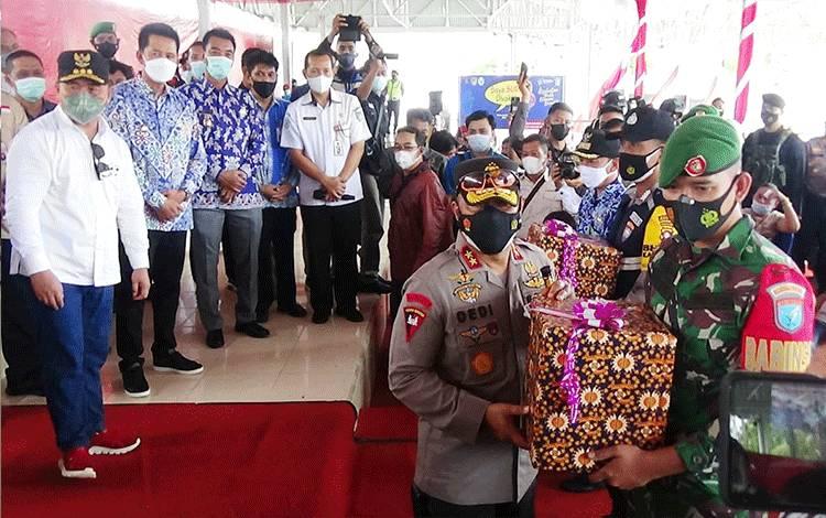 Kapolda Kalimantan tengah Irjen Pol Dr Dedi Prasetyo M Hum saat menyerahkan tali asil dan masker secara simbolis kepada babinsa, Sabtu 12 Juni 2021.