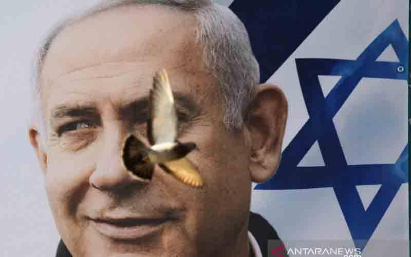 Seekor burung terbang di depan spanduk kampanye partai Likud dengan gambar pemimpin mereka Perdana Menteri Israel Benjamin Netanyahu, menjelang pemilihan 23 Maret mendatang, di kota bagian utara perbatasan Israel-Arab, Nazareth, Sabtu (13/3/2021). (foto : REUTERS/Amir Cohen)