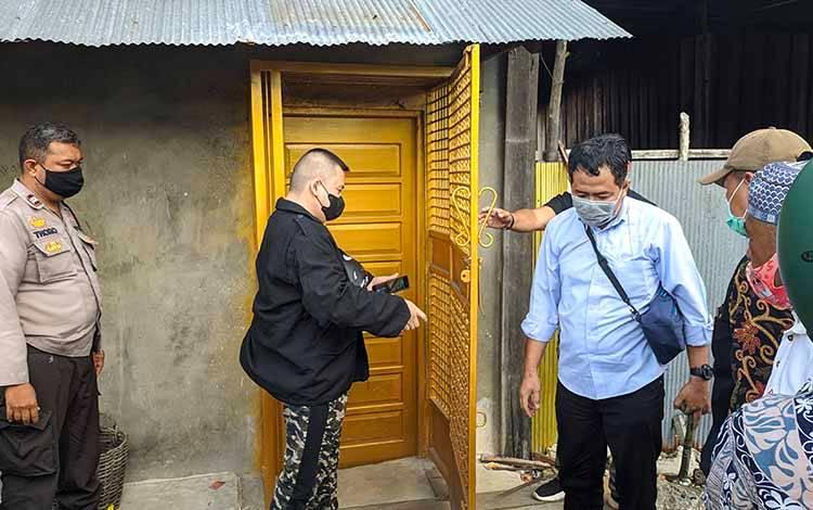 Keluarga pria yang berada di dalam video pemergokan Wakil Bupati Kotim Irawati terhadap toko penjualan miras, saat membuka pintu dengan disaksikan aparat kepolisian