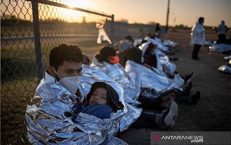 Dustin, seorang migran pencari suaka dari Honduras, memeluk anak lelakinya Jerrardo yag berusia 6 tahun, saat mereka bangun saat matahari terbit di samping mereka yang mengambil tempat beristirahat di dekat lapangan baseball setelah menyebrangi sungai Rio Grande masuk ke Amerika Serikat dari Meksiko dengan rakit, di La Joya, Texas, Amerika Serikat, Jumat (19/3/2021). Selimut darurat diberikan kepada 150 migran asal Amerika Tengah oleh agen Patroli Perbatasan Amerika Serikat. ANTARA FOTO/REUTERS/
