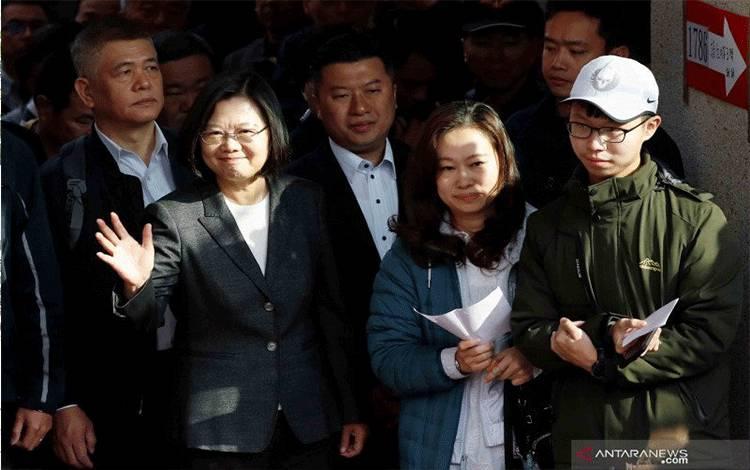 Presiden Taiwan Tsai Ing-wen (kedua kiri) melambaikan tangan saat tiba untuk menggunakan hak pilihnya di sebuah tempat pemungutan suara saat Pemilihan Umum di New Taipei City, Taipei, Taiwan, Sabtu (11/1/2020). Taiwan melaksanakan Pemilu presiden dan parlemen pada hari Sabtu ini dengan pengawasan ketat dari Beijing, meski mengklaim sebagai pulau demokrasi, dalam bayang-bayang protes anti-pemerintah di Hong Kong. ANTARA FOTO/REUTERS/Tyrone Siu/wsj.
