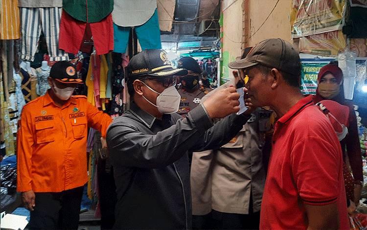 Ketua DPRD Kobar Rusdi Gozali saat memakaikan masker pada pedagang di Pasar Indra Sari Pangkalan Bun.