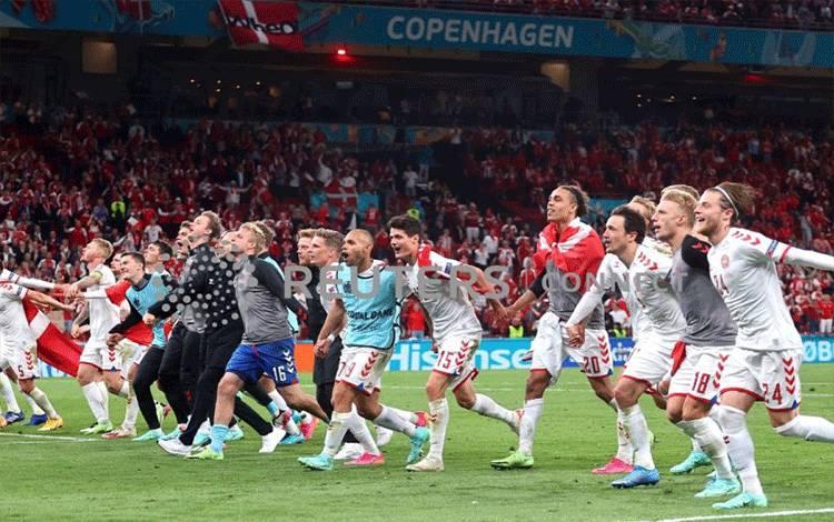 """Para pemain dan staf Denmark merayakan keberhasilan mereka yang secara dramatis lolos ke 16 besar Euro 2020 setelah menjadi runner up usai mengalahkan Rusia 4-1 di Parken Stadium, Copenhagen, Denmark, 21 Juni 2021, dan """"dibantu"""" oleh kemenangan 2-0 Belgia atas Finlandia dalam pertandingan lain Grup B. Belgia memuncaki grup ini dengan sembilan poin. (Pool via REUTERS/Wolfgang Rattay) (REUTERS)"""