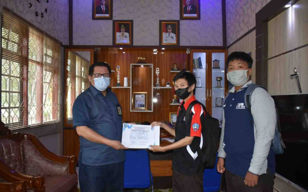 Kepala Diskominfo Kapuas, Junaidi saat menyerahkan sertifikat magang kepada Siswa SMKN 1 Kuala Kapuas pada Jumat, 25 Juni 2021.