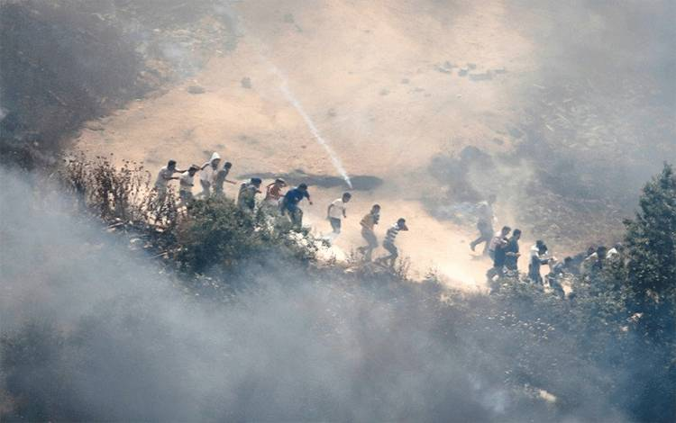 Demonstran Palestina melarikan diri dari gas air mata yang ditembakkan oleh pasukan Israel selama protes terhadap pemukiman Israel, di West Bank yang diduduki Israel, Jumat (28/5/2021). ANTARA FOTO/REUTERS/Raneen Sawafta/RWA/sa. (REUTERS/RANEEN SAWAFTA)