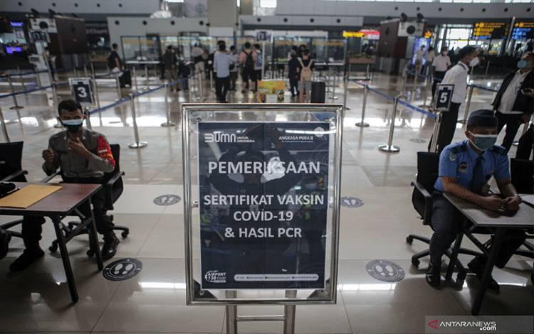 Petugas memeriksa surat vaksinasi dan hasil tes PCR calon penumpang pesawat sebelum melakukan penerbangan di Terminal 3 Bandara Internasional Soekarno Hatta, Tangerang, Banten, Senin (5/7/2021). ANTARA FOTO/Fauzan/pras.