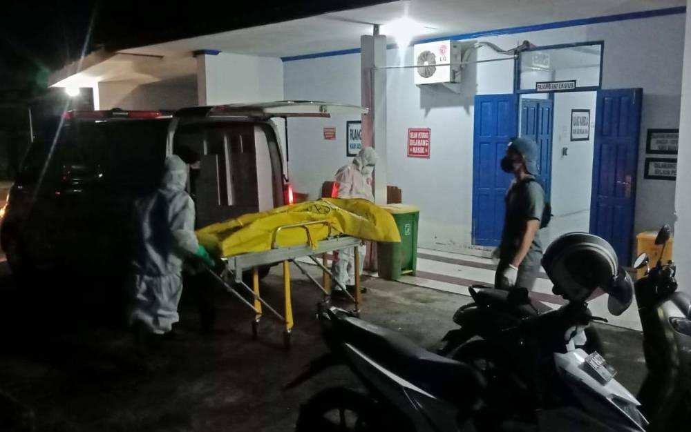 Petugas mengevakuasi jenazah pria yang ditemukan tergeletak di depan SPBU Raut, Buntok, Jumat malam, 17 Juli 2021.