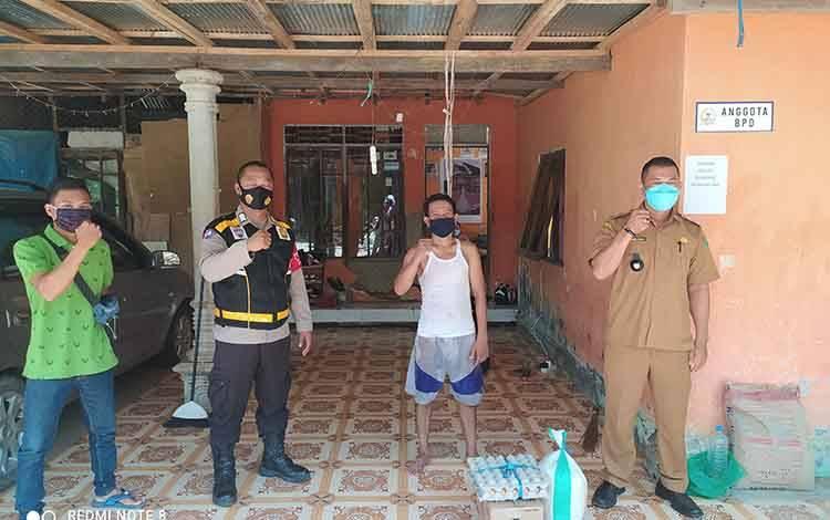 Kepala Desa Gohong beserta bhabinkamtibmas memberikan bantuan sembako kepada warga yang menjalani isolasi mandiri.