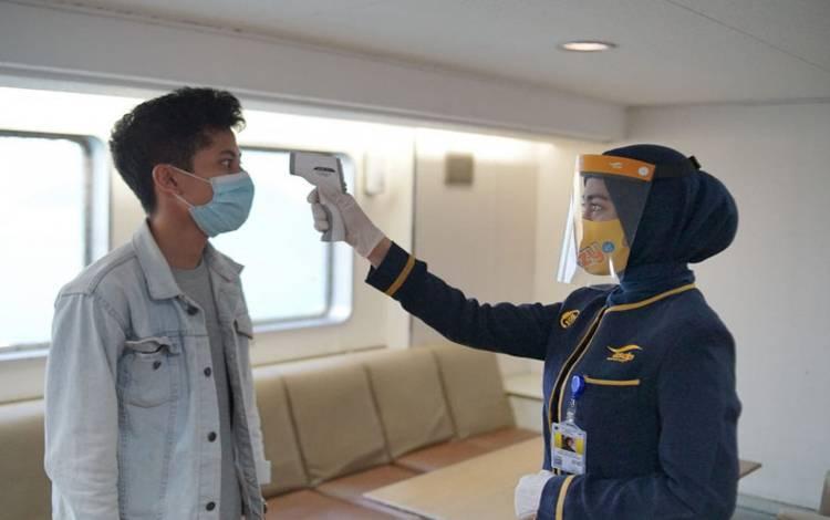 Pengecekan suhu oleh petugas kapal kepada pengguna jasa penyeberangan