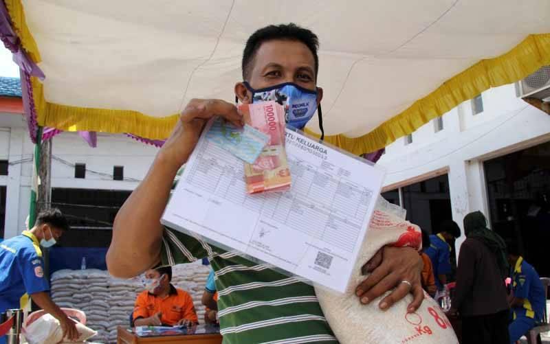Ilustrasi - Seorang warga memperlihat sejumlah uang dan beras bantuan sosial (bansos) dari pemerintah pusat di Kantor Pos Dumai, Riau, Selasa (27/7/2021). (foto : ANTARA FOTO/Aswaddy Hamid/foc)