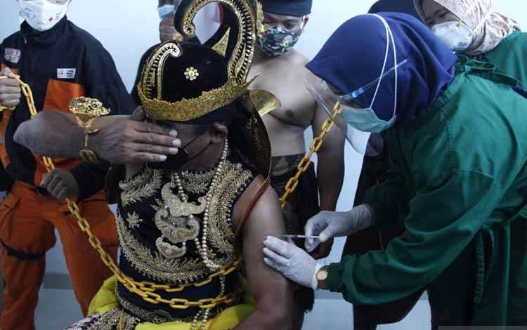 Petugas menyuntikkan vaksin COVID-19 kepada penerima vaksin berkostum wayang di RSUD Bung Karno, Solo, Jawa Tengah, Januari 2021
