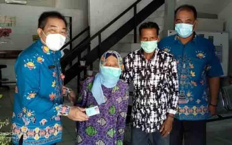 Plt Kepala Disdukcapil Kapuas, Sipie S Bungai saat menyerahkan dokumen kependudukan kepada warga lansia, Kamis 5 Agustus 2021.