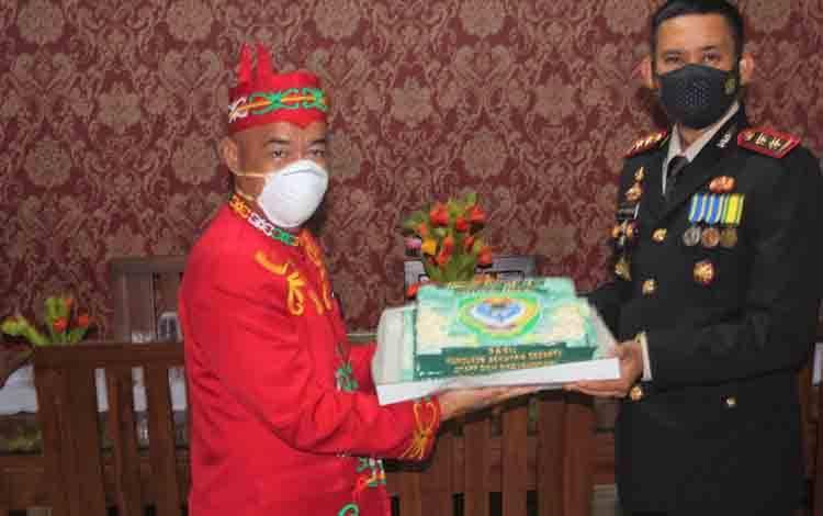 Kapolres menyerahkan kue tart kepada Bupati Seruyan