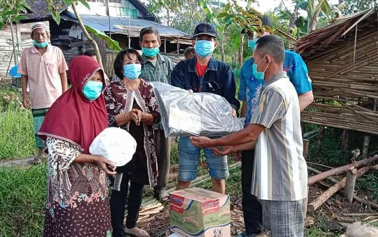 Camat Pulau Petak Seflihi saat menyerahkan bantuan kepada warga tertimpa musibah kebakaran rumah di Desa Saka Lagun, Kamis, 5 Agustus 2021.
