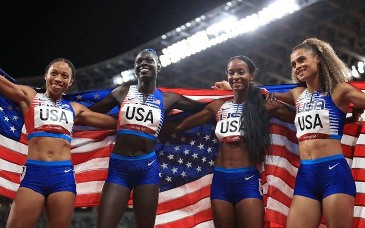 Kuarter pelari putri Amerika Serikat Sydney McLaughlin, Allyson Felix, Dalilah Muhammad dan Athing Mu, membentangkan bendera Amerika Serikat setelah menyabet medali emas estafet 4x400 meter putri di Olympic Stadium, Tokyo, Jepang, 7 Agustus 2021. (REUTERS/HANNAH MCKAY)