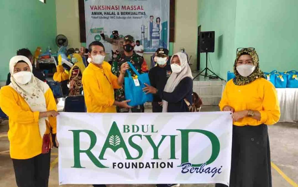 Penyerahan bingkisan pada warga yang diwakili Kades Natai Baru dalam kegiatan vaksinasi massal di desa tersebut, Minggu, 15 Agustus 2021