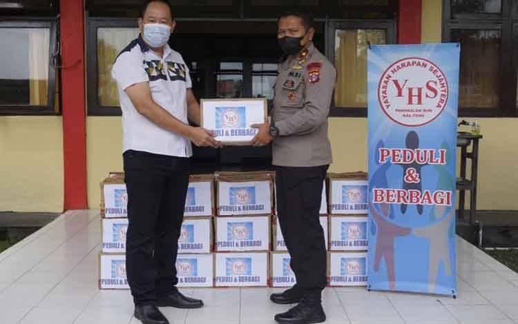 Danyon B Pelopor Satbrimob Polda Kalteng, Kompol I Gede Putra menerima paket sembako dari Hartono Halim, pengurus YHS Pangkalan Bun untuk didistribusikan kepada korban banjir.