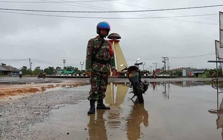 Babinsa Kelurahan Baru, Serda Eko Pujo saat mengecek luapan air di sepuraran Bundaran Tudung Saji.