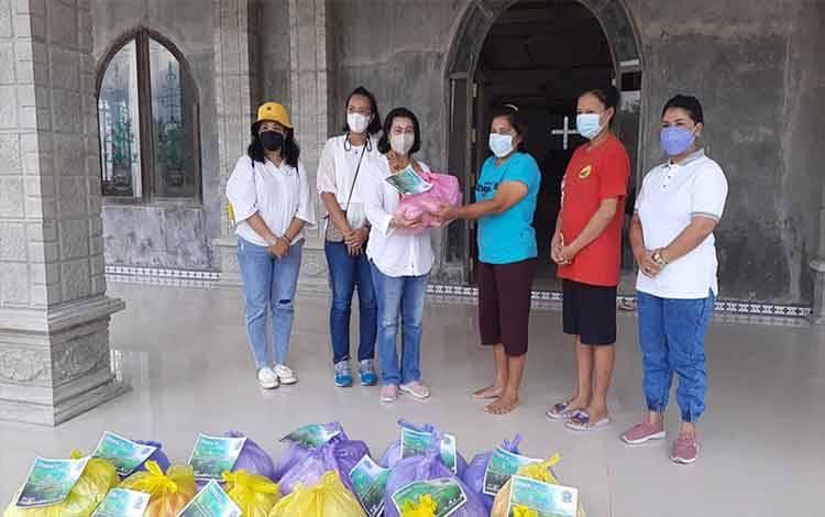 Ketua DPC PWKI Kabupaten Gumas, Rayaniatie Djangkan dan jajaran saat menyalurkan bantuan kepada warga di Desa Tumbang Tariak, Sabtu, 18 September 2021.
