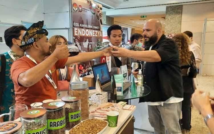 Barista dari Indonesia menyerahkan segelas kopi kepada pengunjung di pameran kopi Coffex Istanbul 2021. Melalui tajuk Heaven of Specialty Coffee sukses menarik minat pengunjung dan menedapatkan komitmen pembelian 30 kontainer atau 600 ton biji kopi melalui pameran tersebut di Istanbul, Turki. (KJRI Istanbul)