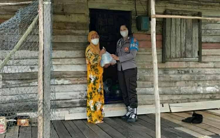 Personel Polwan Polres Kapuas saat menyalurkan bantuan sembako untuk warga di Kecamatan Selat.