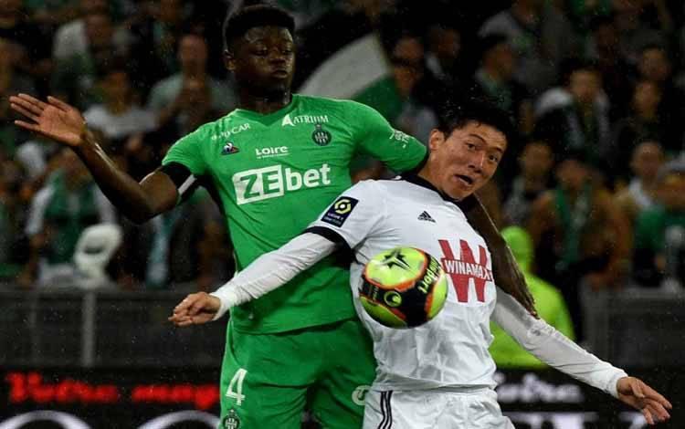 Striker Bordeaux Ui-jo Hwang (kanan) berduel dengan bek Saint-Etienne Saidou Sow dalam pertandingan Liga Prancis di Geoffroy-Guichard Stadium di Saint-Etienne, Prancis, 18 September 2021. Dua gol Hwang membawa Bordeaux menang 2-1