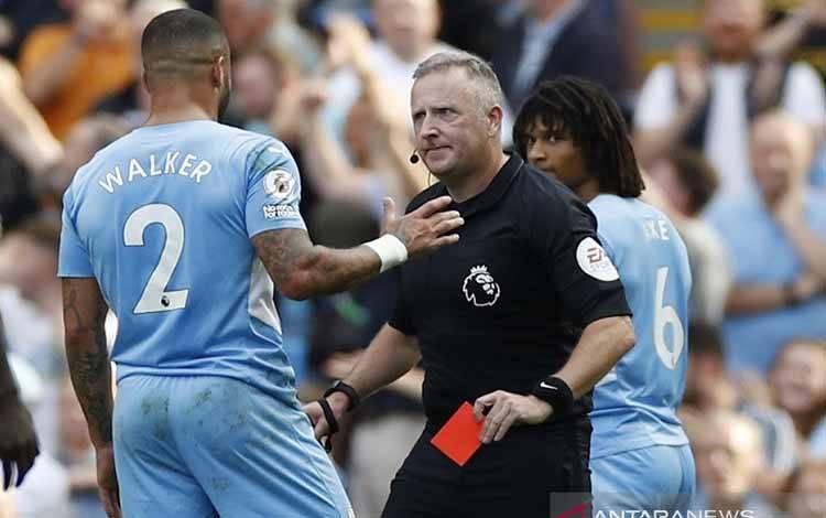 Wasit Jonathan Moss (kanan) memberi kartu merah kepada bek sayap Manchester City Kyle Walker sebelum menganulirnya atas petunjuk VAR dalam laga lanjutan Liga Inggris melawan Southampton di Stadion Etihad, Manchester, Inggris, Sabtu (18/9/2021)