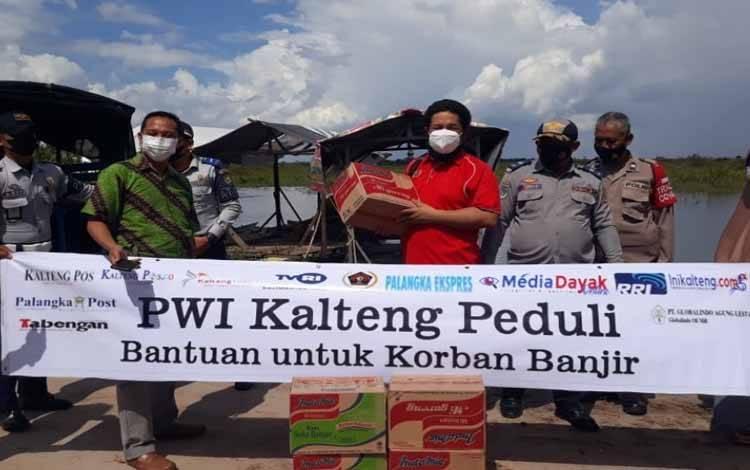 Ketua PWI Kalteng, Harris Sadikin bersama tim PWI saat penyaluran bantuan korban banjir di Kota Palangka Raya