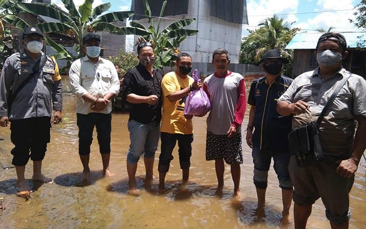 Anggota PWI Barsel didampingi Bhabinkamtibmas membagikan sembako kepada warga terdampak banjir di Desa Kalahien.