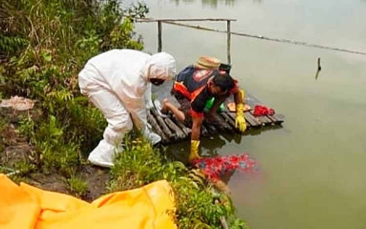 Anggota Polsek Benua Lima mengevakuasi mayat korban dari embung