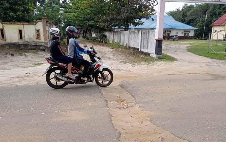 Pengendara sepeda motor memperlambat laju kendaraan saat melintasi bekas galian di depan kantor Dinas Pendidikan Barito Timur.