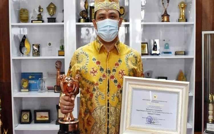 Bupati Lamandau, Hendra Lesmana memegang penghargaan APE dari Kementerian PPPA