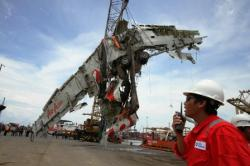 TANJUNG PRIOK: Badan pesawat AirAsia QZ8501 dipindahkan dari kapal Crest Onyx, saat tiba di Pelabuhan Tanjung Priok, Jakarta Utara, Senin (2/3). Serpihan badan utama pesawat tersebut selanjutnya diserahkan kepada Komite Nasional Keselamatan Transportasi (KNKT) untuk dilakukan penyelidikan.