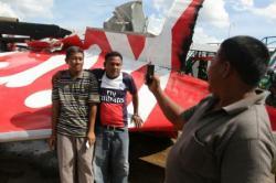 SELFIE AIRASIA: Warga berfoto, berselfie-ria di depan puing ekor pesawat AirAsia QZ8501 di Pelabuhan Kumai, Pangkalan Bun, Kalimantan Tengah, Senin (12/1). Menurut Presiden Direktur AirAsia Indonesia, Sunu Widiyatmoko, Selasa (3/3), baru 2 ahli waris korban yang selesai urusan klaim asuransi.