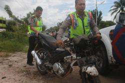 DIEVAKUASI: Dua aparat kepolisian dari Unit Laka Polres Palangka Raya mengevakuasi sepeda motor Yamaha Vixion milik Dodi pascaterlibat kecelakaan lalu lintas dengan Honda Beat di Jalan G Obos Induk, Selasa (3/3).