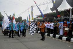PAWAI TAARUF : Bupati Barito Utara H Nadalsyah mengibarkan bendera 'Start' saat melepas para kafilah dalam Pawai Taaruf STQ ke 46 tingkat Kabupaten Barito Utara di depan gedung Balai Antang Muara Teweh, Rabu (4/3).