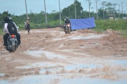 MENGAIS REZEKI: Rusaknya jalan Pangkalan Bun-Kolam dimanfaatkan oleh masyarakat sekitar untuk mengais rezeki dengan memperbaiki jalan menggunakan mating-mating.