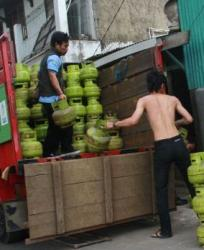 GAS ELPIJI : Dua karyawan sedang mengangkut tabung gas elpiji ke atas truk yang akan didistribusikan ke pelanggan.